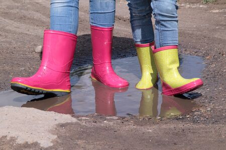 Childrens legs in jeans in rain rubber boots standing in a puddle in the sun