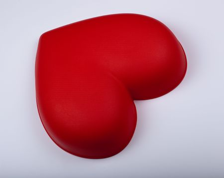 plastic heart: Red plastic heart lies on a white plastic background.