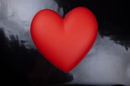 plastic heart: Red plastic heart lies on a black background.