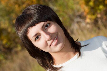 aureate: Portrait of the nice girl-brunette against the autumn nature. Stock Photo