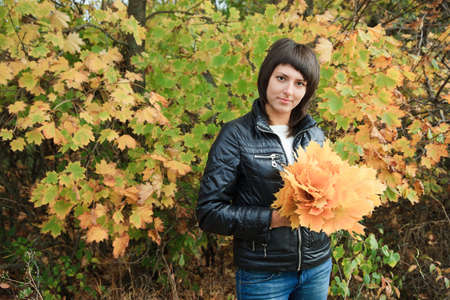 aureate: Portrait of the nice girl-brunette against the autumn nature with a bouquet of yellow leaves of a maple.