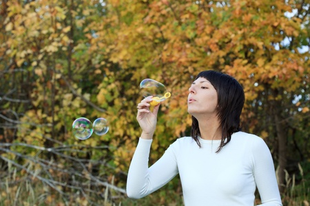 aureate: The girl starts up soap bubbles against yellow autumn foliage.
