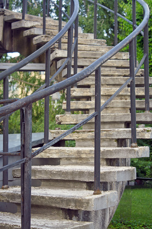 banisters: A spiral staircase with concrete steps and banisters of the colored tubes