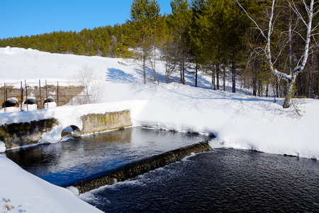 spillway: Winter in Siberia. Freezing spillway on the pond