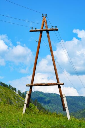 siberia: Power line with the supports of logs in mountain area