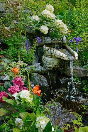 Small decorative fountain in the garden decorated with flowers
