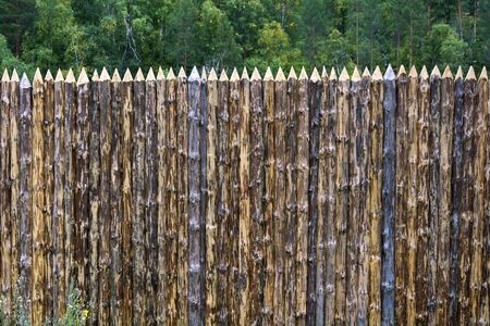 New decorative fence made of freshly cut pointed logs