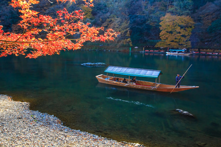 KYOTO, JAPAN - DECEMBER 3: Sailing boat in Kyoto, Japan on December 3, 2012. Unidentified people sail boates in the Oi river for tourist who travel to Arashiyama mountain area Editorial