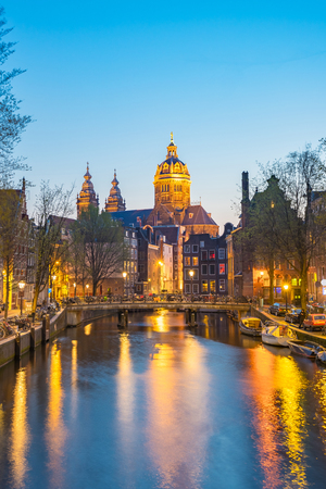 Night in Amsterdam with the Basilica of St. Nicholas in Amsterdam city, Netherlands.