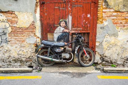 Penang, Malaisie - 21 mai 2016: La peinture d'un garçon assis sur une vieille moto à George Town, Penang, en Malaisie.