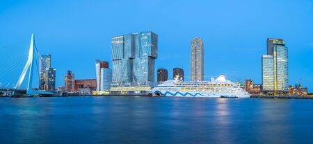 Panorama view of Erasmus Bridge and Rotterdam skyline at night in Rotterdam, Netherlands.