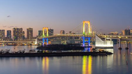 Tokyo city skyline at night with view of Rainbow bridge in Japan.