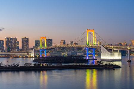 Tokyo skyline at night with view of Rainbow bridge in Japan.