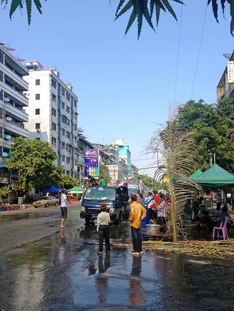 YANGON, MYANMAR - APRIL 16, 2013 :Day traffic moves easily past the water platforms during the Thingyan Water Festival in Yangon, Myanmar