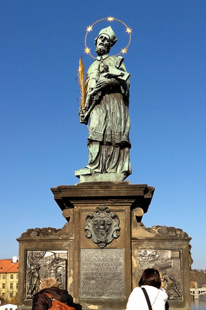 ensures: Prague, Czech Republic - NOVEMBER 13, 2012 : statue of John of Nepomuk in Prague on the Charles Bridge on the background of blue sky, the oldest one on the bridge. Touching it brings good fortune and ensures returning to the city of Prague. Editorial