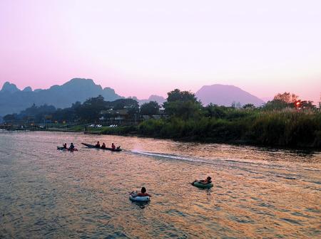 tubing: Recreation.Tourist kakaking and tubing along the river Nam Song at sunrise. Vang Vieng, Laos.