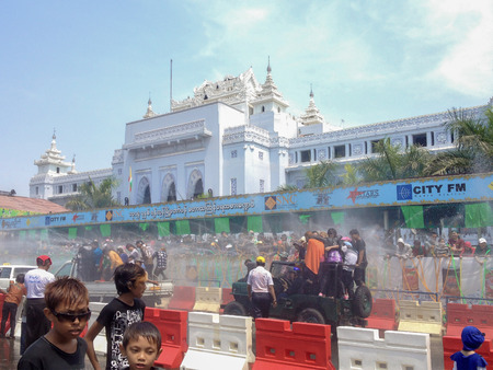 YANGON, MYANMAR - APRIL 15, 2013 :Thingyan Festival at Yangon City Hall  in Yangon, Myanmar.View of people and pick-ups passing by Yangon City Hall during The Thingyan Water Festival Celebration.