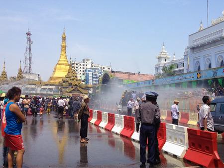 YANGON, MYANMAR - APRIL 15, 2013 :Thingyan Festival at Sule Paya Pagoda  in Yangon, Myanmar.View of people and pick-ups passing by Sule Paya Pagoda  during The Thingyan Water Festival Celebration.