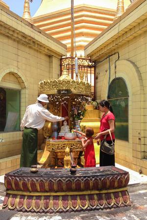 YANGON, MYANMAR - APRIL 15, 2013 : Prayers at Buddhist temple