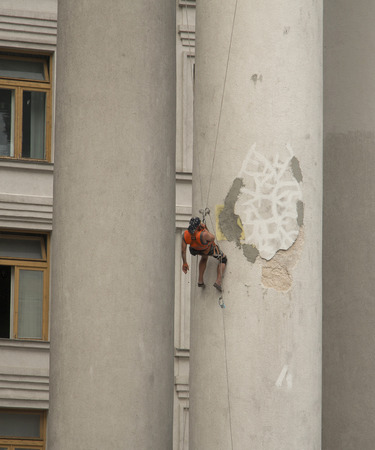 Industrial climber talking on the phone at the height of