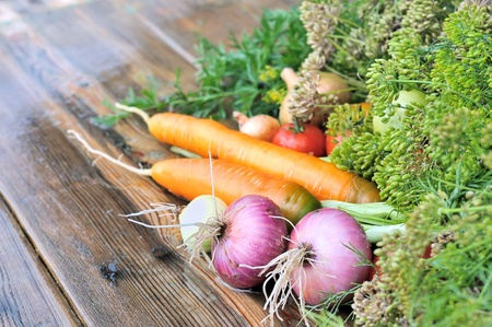 Vegetables on the table. Onions and carrots on a wet wooden table. Fresh vegetables. Table for cooking food. Stock Photo