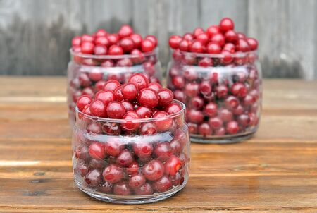 Fresh cherries. Cherries in glass jars. Cherry on a wooden table. Harvesting of berries for the winter. Stock Photo