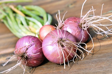 Onions on the table. Red onions. Group onions on a wet wooden table. Fresh vegetables. Wooden table. Stock Photo