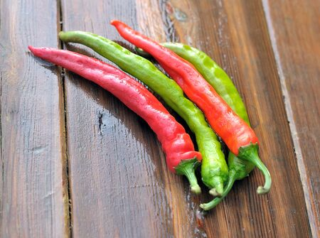 Pepper. Red and green pepper. Peppers on a wooden table.