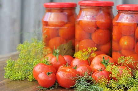 Fresh tomatoes. Canned tomatoes. tomatoes in a glass jar on a wooden table.