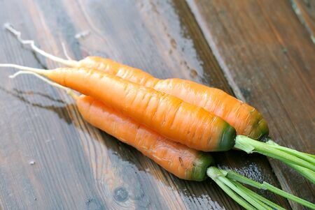 Carrots. Carrot on a wet wooden table. Stock Photo