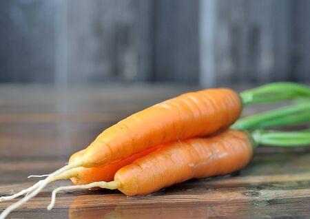 naranjas: Zanahorias. Zanahoria en una tabla de madera húmeda. Foto de archivo