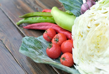 Vegetables on a wooden table. Cabbage, tomatoes, pepper, garlic on a wet table. Fresh vegetables.