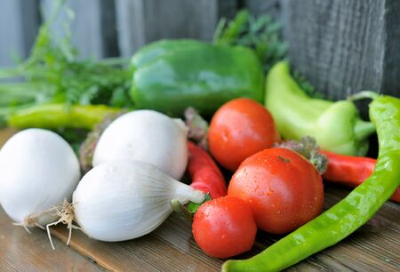 Vegetables on a wooden table. Tomatoes, peppers, onions on a wet table. Fresh vegetables.