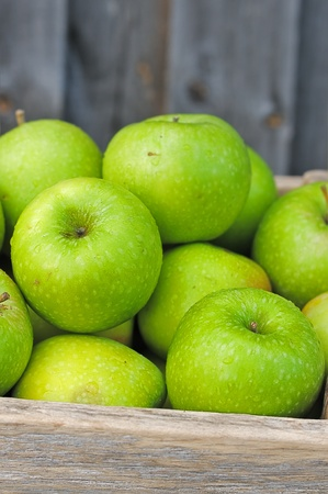 Green apples in a wooden box. Bunch of ripe apples. photo