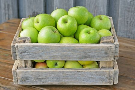 Green apples in a box on a wooden table. photo