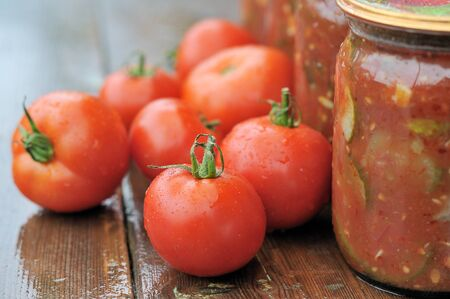 tomatos: Tomatoes and jars of canned vegetables.