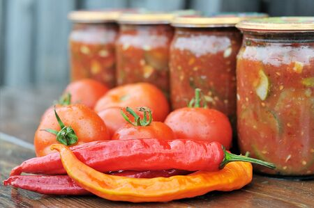 Peppers tomatoes on a wooden table. Glass jars with canned vegetables