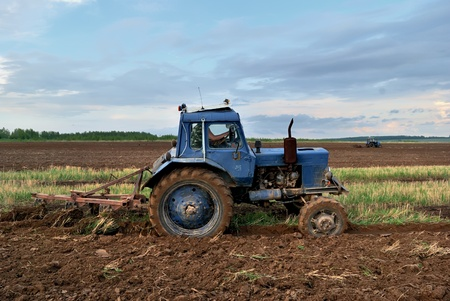 Tractor in the field. Plowing the land. photo