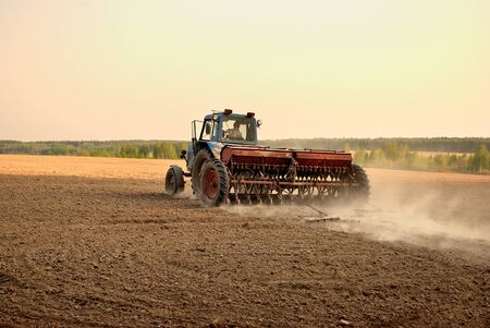 plough land: Tractor in the field. Plowing the land. Agricultural work. Editorial
