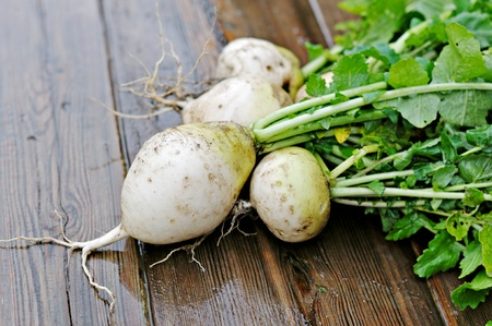 Turnips with green tops on a wooden table.
