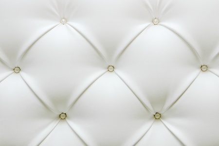 upholstery: Leather upholstery. White leather with pearl buttons. Background of expensive furniture. The texture of quilted furniture.