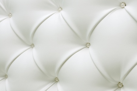 Quilted white leather with white pearls. Leather upholstery. White leather with pearl buttons. Background of expensive furniture. The texture of quilted furniture. photo