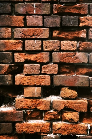 Old crumbling brick wall. A wall of red brick.