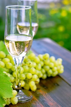 glass of wine on a wooden table. Bunches of grapes. Stock Photo - 12566594