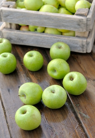 scattered: Green apples in a box. Scattered on the table apples.