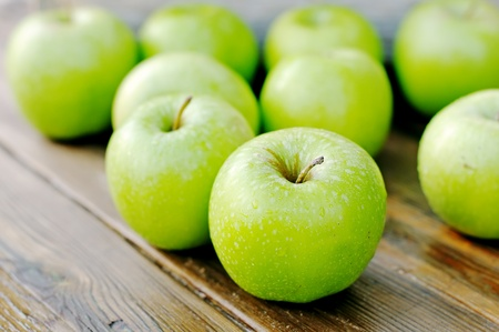 green apples on a wooden table.