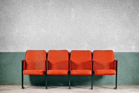 Orange seats from the old gray walls  A number of four seats  Chairs against the wall