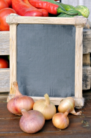 Products on the market. onions and the price tag in a wooden frame. Price list for food.