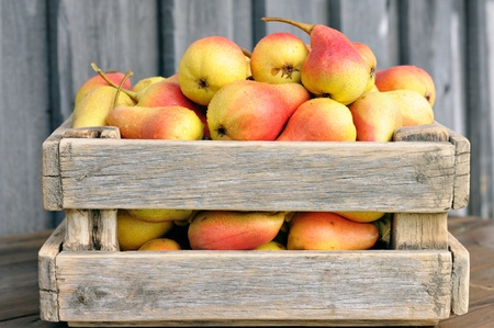 Ripe pears in a wooden box on the table.