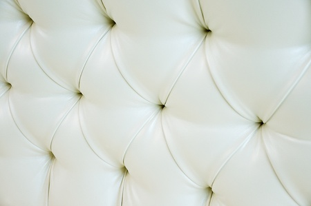 Quilted white leather with white pearls  Leather upholstery  White leather with pearl buttons  Background of expensive furniture  The texture of quilted furniture  photo